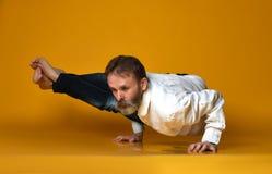 Stary człowiek ćwiczy joga robi rozciąganiu ćwiczy przeciw żółtemu tłu obrazy royalty free