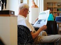 Stary człowiek czyta gazetę w bibliotece Szwecja, Sztokholm - Zdjęcie Stock