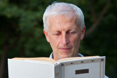 Stary człowiek czytelnicza książka obraz stock