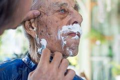 Stary człowiek dostaje jego brodę golił młodym wykwalifikowanym mężczyzna w domu Obraz Royalty Free
