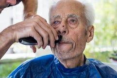 Stary człowiek dostaje jego brodę golił młodym wykwalifikowanym mężczyzna w domu Obrazy Royalty Free