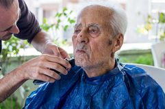 Stary człowiek dostaje jego brodę golił młodym wykwalifikowanym mężczyzna w domu Zdjęcie Royalty Free