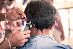 Stary człowiek ma ostrzyżenie z w fryzjera męskiego sklepie włosiani cążki Fotografia Royalty Free
