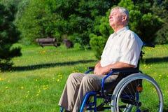 Stary człowiek na wózku inwalidzkim cieszy się światło słoneczne Zdjęcia Stock