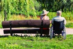 Stary człowiek na wózku inwalidzkim i młodej kobiecie na ławce Obrazy Royalty Free