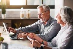 Stary człowiek pisać na maszynie podczas gdy kobieta wskazuje przy ekranem obraz royalty free