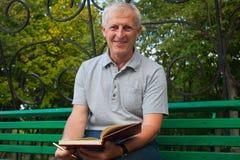 Stary człowiek pisze nutowej książce obrazy stock