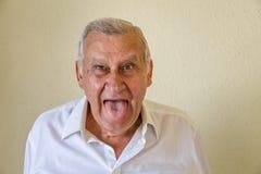 Stary człowiek pokazuje jęzor Fotografia Stock