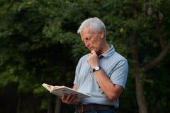 Stary człowiek pozycja i czytelnicza książka fotografia royalty free
