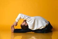 Stary człowiek praktyk Ashtanga Vinyasa joga plecy chylenia asana Paschimottanasana - posadzony przedni chył obrazy royalty free