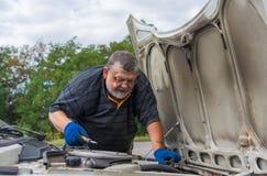 Stary człowiek robi samochód naprawie Obrazy Royalty Free