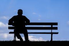 Stary człowiek siedzi samotnie na parkowej ławce pod drzewem Fotografia Royalty Free