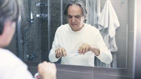 Stary człowiek szczotkuje zęby przed lustrem fotografia stock