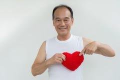 Stary człowiek trzyma czerwonego serce na białym tle na białej koszula Zdjęcie Stock