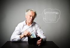 Stary człowiek w bielu i portfel z dwadzieścia euro Grzejny sezon, podatki i oszczędzania pojęcie, grzejnik zdjęcie stock