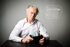 Stary człowiek w bielu i portfel z dwadzieścia euro Grzejny sezon, podatki i oszczędzania pojęcie, grzejnik fotografia stock