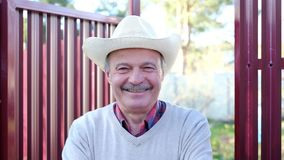 Stary człowiek w kapeluszowy uśmiechnięty trwanie plenerowym zbiory