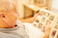 Stary człowiek z demencji spojrzeniami przy albumem fotograficznym fotografia royalty free