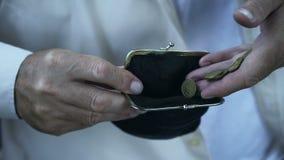 Stary człowiek z drżącej ręki kładzenia monetami w portflu, emeryta ubóstwo, budżet zdjęcie wideo