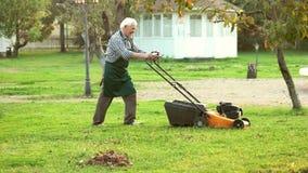 Stary człowiek z gazonu kosiarzem zbiory wideo