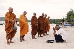 Stary człowiek daje jedzeniu i napojowi dla datków mnichów buddyjskich Zdjęcia Stock
