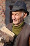 Stary człowiek niesie drewno obrazy stock