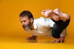 Stary cz?owiek ?wiczy joga robi rozci?ganiu ?wiczy przeciw ? fotografia royalty free