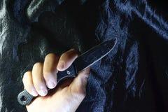 Stary czarny falcowanie nóż na czarnej tkaninie jest błyszczący zdjęcia stock