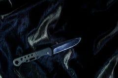 Stary czarny falcowanie nóż na czarnej tkaninie jest błyszczący obrazy stock