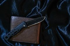 Stary czarny falcowanie nóż na czarnej tkaninie jest błyszczący zdjęcia royalty free