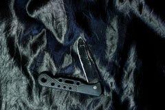 Stary czarny falcowanie nóż na czarnej tkaninie jest błyszczący fotografia royalty free