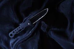 Stary czarny falcowanie nóż na czarnej tkaninie jest błyszczący obraz stock