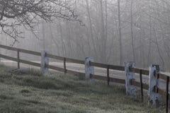 Stary czerwieni ogrodzenie przy wiejską drogą mgłowy ranek Zdjęcia Stock