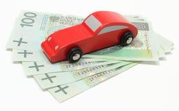 Stary czerwieni zabawki samochód z pieniądze na białym tle Fotografia Stock