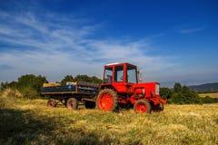 Stary czerwony ciągnik na rolniczym polu Zdjęcia Royalty Free