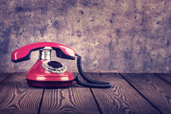 Stary czerwony telefon na drewnianym stole Obrazy Stock