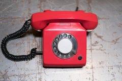 Stary czerwony telefon na stole - rocznika telefon na biurku Zdjęcia Royalty Free