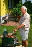 stary człowiek gotowania na zewnątrz. Zdjęcia Royalty Free