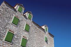 Stary dom z zielonymi okno na kamieniu budował fasadę Zdjęcia Stock