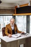 Stary dramatopisarz w eleganckim kostiumu pisze scenariusz film indoors obrazy stock