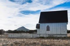 Stary drewniany budynek z białym palika ogrodzeniem out stać na czele na prerii Obraz Stock