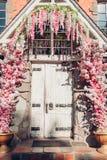 Stary drewniany drzwi dekorujący z bielu i menchii kwiatami Zewnętrzny projekt Cukierniany wejście obrazy stock