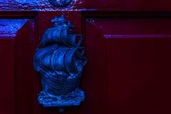 Stary drewniany drzwi mieścić z mosiężnym knocker kształtował żeglowanie statek Fotografia Stock