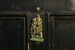 Stary drewniany drzwi mieścić z mosiężnym knocker kształtował żeglowanie statek Zdjęcia Stock