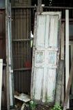 Stary drewniany drzwiowy opierać przeciw starej ośniedziałej metalu baru ścianie Fotografia Stock