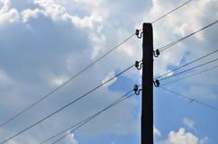 Stary drewniany elektryczny słup dla przekazu depeszująca elektryczność na tle chmurny niebieskie niebo Przestarzała metoda uzupe Zdjęcie Royalty Free