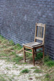 Stary drewniany krzesło przeciw ściana z cegieł Obraz Royalty Free