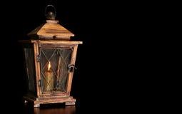 Stary drewniany lampion z płonącą świeczką odizolowywającą na czarnym tle obrazy stock