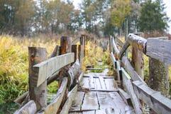 Stary, drewniany, obdrapany most przez zaniechaną rzekę w lesie, Fotografia Stock