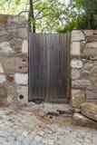 Stary drewniany ogrodowy drzwi na skłonie w ogród z kamiennymi ścianami przy Tenedos Bozcaada wyspą morzem egejskim obrazy stock